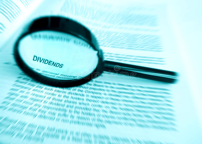 Focus on dividends. A photograph image of a magnifier glass focused on the word dividend on an annual company report. Concept picture for investment and returns royalty free stock photography