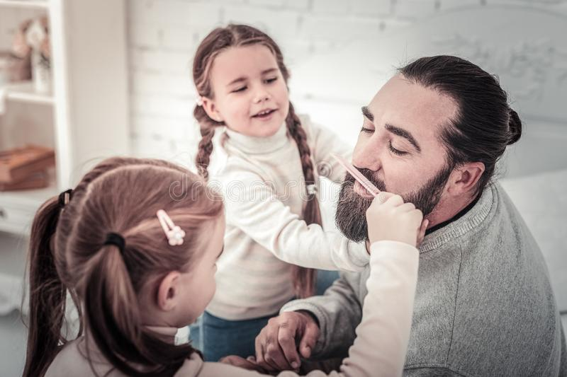 Focus on father having his beard comed by his cute children royalty free stock image