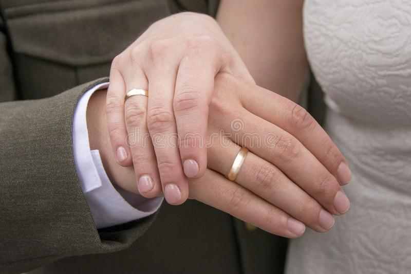 Hands of just married with golden rings on fingers stock image