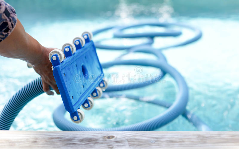 Focus on front roller of equipment cleaning swimming pool royalty free stock photography