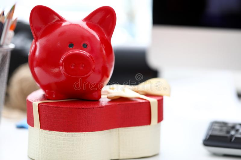Red piggy bank. Focus on golden presenting ribbon tied on big cardboard oval shaped box. Someone put case full of joyful presents on table in modern high-tech stock images