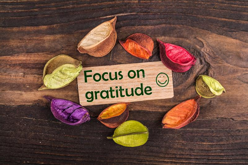 Focus on gratitude with happy face. In wooden card with dried flower on wood stock photography