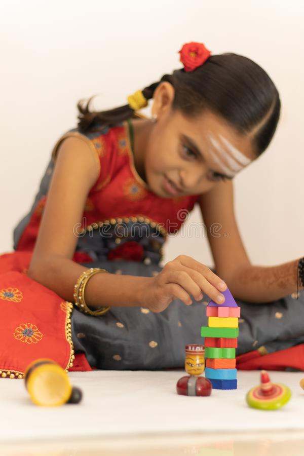 Focus on hands of cute little child girl playing with colorful wooden blocks in the room royalty free stock photo