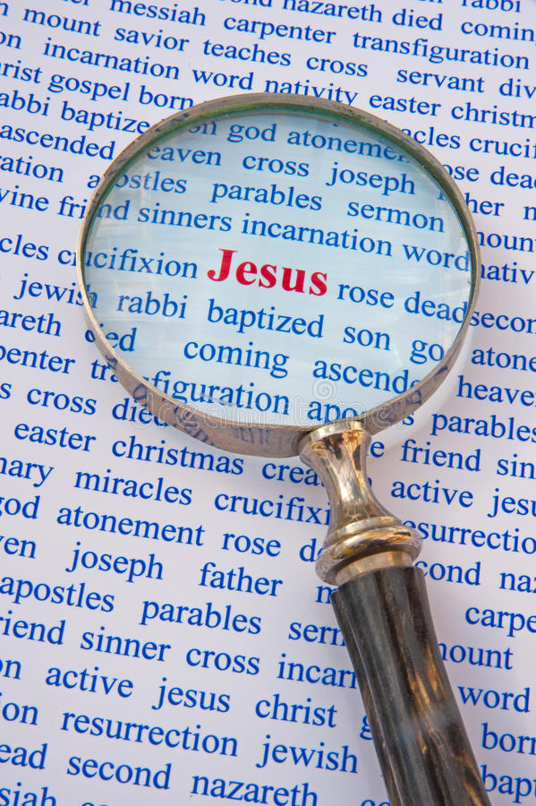 Focus on Jesus. Text Jesus in red surrounded by words in blue relating to his life story. A hand magnifier focuses attention on the name royalty free stock photography