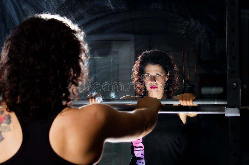 Focus Before Lifting. A weight trainer focuses in the mirror before lifting the barbell. Dramatic lighting intensifies the mood of the scene stock images
