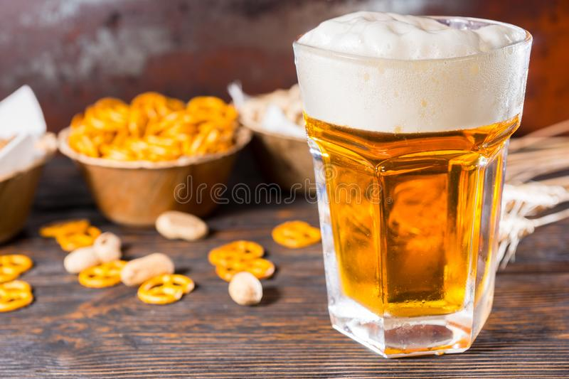 Focus on light beer and a head of foam near plate with small pretzel on dark wooden desk stock photo