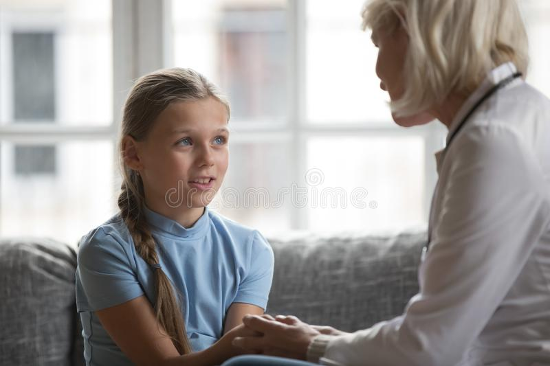 Focus on little girl holding hands aged therapist doctor royalty free stock photography