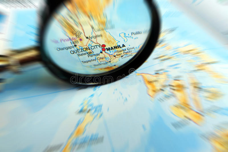 Focus on Manila, Philippines on map. Focusing on Manila city - A photograph showing a magnifying glass looking for and focusing on the famous Asian city of stock photo
