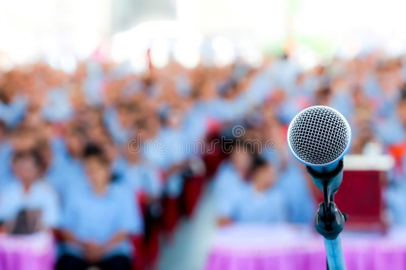 Microphone over the blurred business conference hall or seminar room, Blurred background. royalty free stock photos