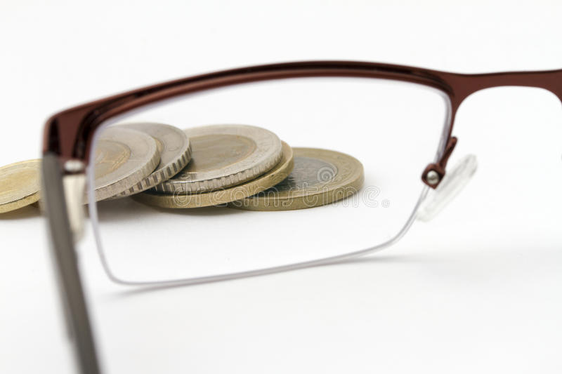 Heap of coins. Some with serrated edges, viewed through the left hand lens of a pair of spectacles, white background stock photos