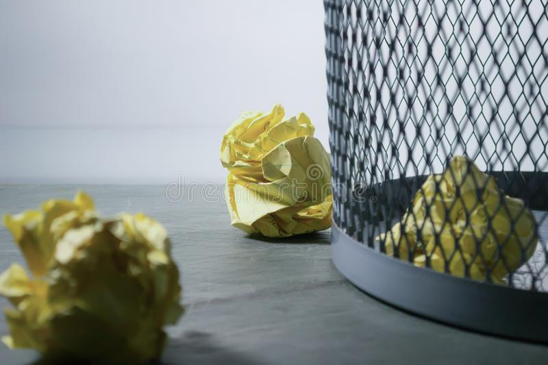 Focus Photo of Yellow Paper Near Trash Can stock photos