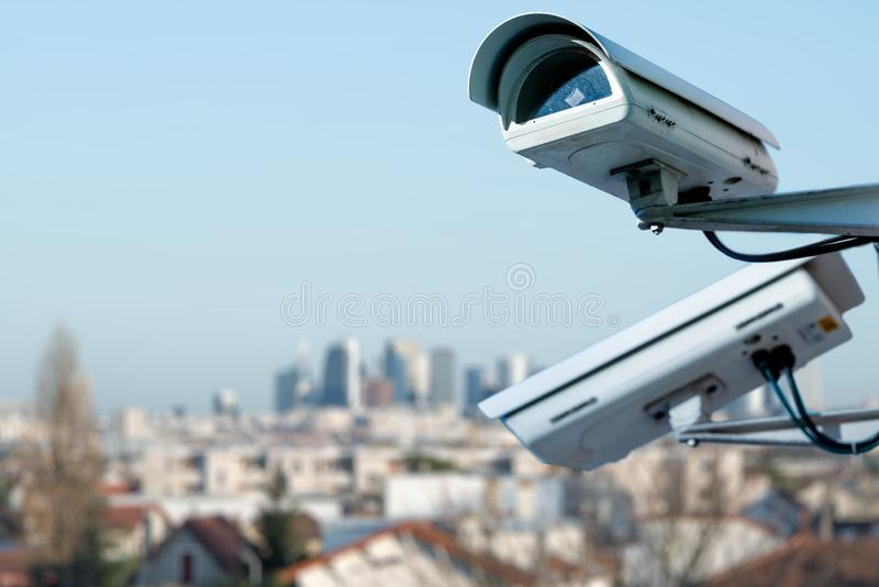 Security CCTV camera monitoring system with panoramic view of a city on blurry background. Focus on security CCTV camera monitoring system with panoramic view of stock photos