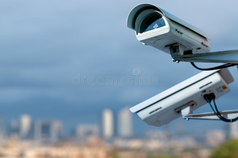 Security CCTV camera monitoring system with panoramic view of a city on blurry background. Focus on security CCTV camera monitoring system with panoramic view of stock image