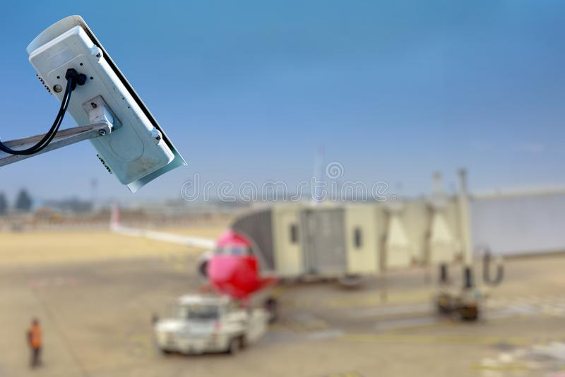 Security CCTV camera or surveillance system with airport tarmac on blurry background. Focus on security CCTV camera or surveillance system with airport tarmac on royalty free stock images