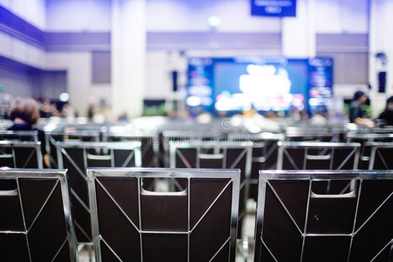 Focus selettivo alle sedie dell'auditorium per le riunioni degli azionisti o per gli eventi del seminario con proiettore sfocato  immagini stock