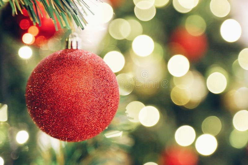 Focus sparkling glitter red ball on blur Christmas tree. And light bokeh in background with copy space royalty free stock photography