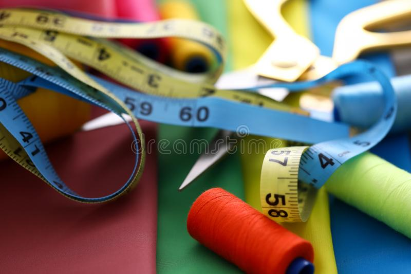 Tools for sewing and handmade. Focus on tailors equipment for creating fashionable clothes. Professional scissors, colorful threads and different measuring tapes royalty free stock image
