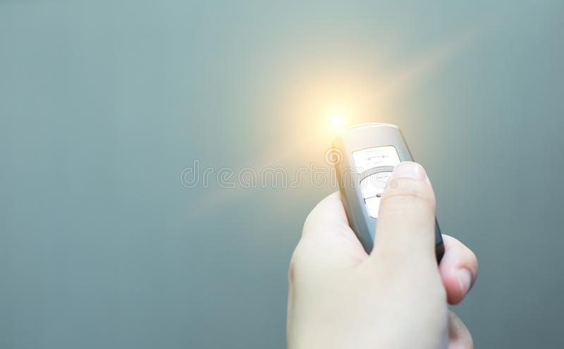 Focus to a hand holding remote controller. There is light effect on it with gray background royalty free stock photography