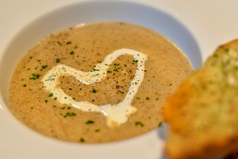 Focus view warm mushroom soup decorated with heart shaped cream royalty free stock images