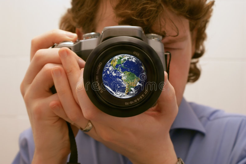 Focus on the World. A photographer taking a picture with the world in the lens. Focus on the world with the photographer blurred. Blue Marble picture courtesy of stock image