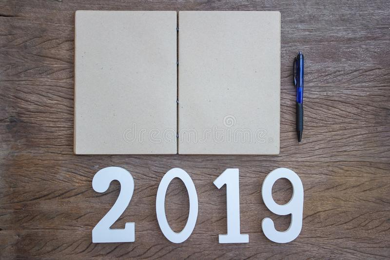 Focus your work plan concept. Top view, flat lay note book and pen with a cut wood number 2019 on wood table. Personal work space for New year resolution stock image