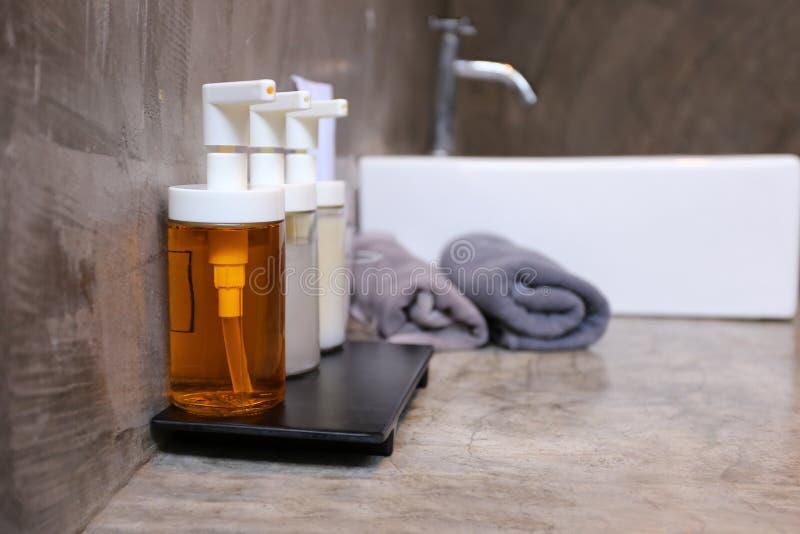 Focuse selectivo de la botella de vidrio de la bomba con el jabón líquido, el champú, la espuma del baño y los accesorios en cuar foto de archivo
