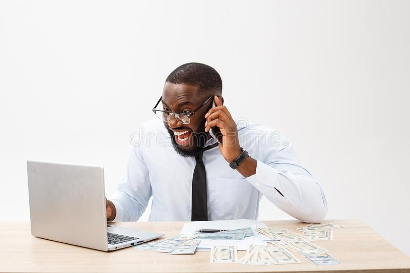 Focused African-American office manager sitting at office with laptop, reading important documents with puzzled royalty free stock images