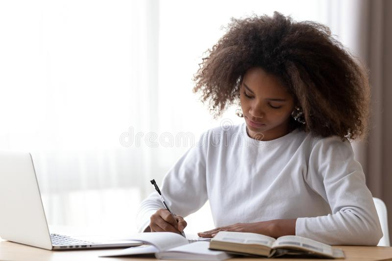 Focused black girl study at home doing homework. Focused African American teenage girl sit at table with laptop studying with handbooks, serious concentrated stock photos