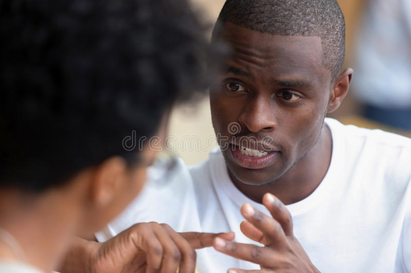 Focused african man having serious talk with woman at meeting. Focused african american men looking speaking to women having business talk negotiating explaining royalty free stock image