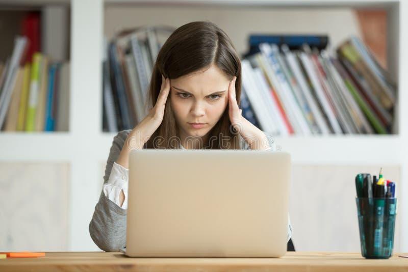 Focused angick flickastudenten som lär svår examen med lapt arkivbilder