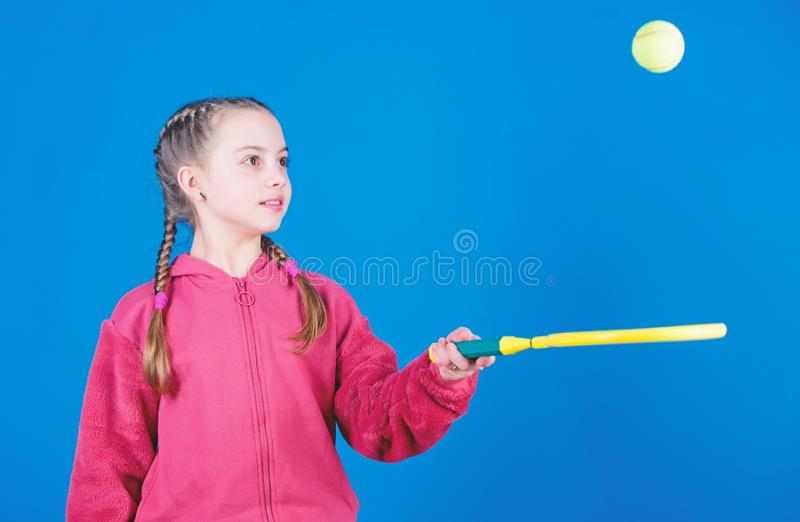 Focused on ball. Girl adorable child play tennis. Practicing tennis skills and having fun. Athlete kid tennis racket on. Blue background. Active leisure and royalty free stock photos