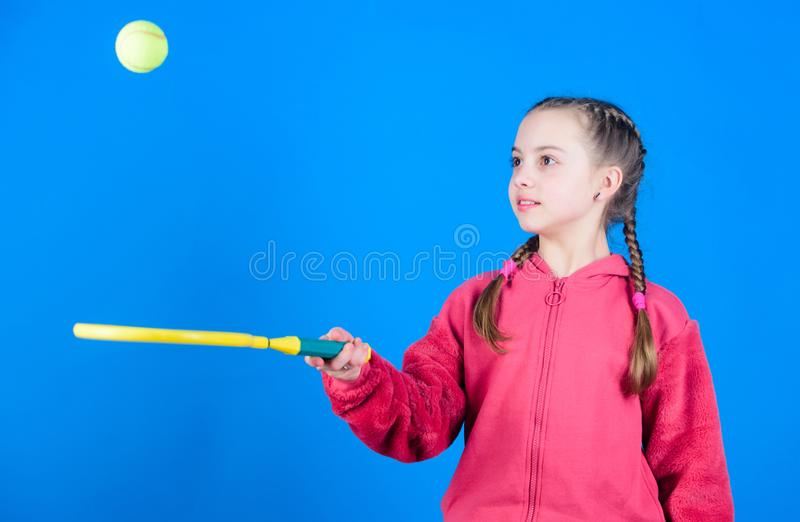 Focused on ball. Girl adorable child play tennis. Practicing tennis skills and having fun. Athlete kid tennis racket on. Blue background. Active leisure and royalty free stock image