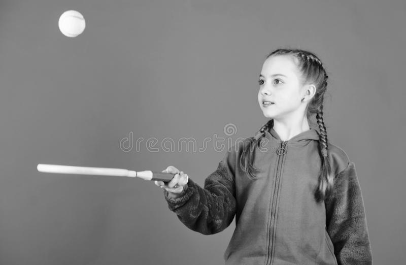 Focused on ball. Girl adorable child play tennis. Practicing tennis skills and having fun. Athlete kid tennis racket on. Blue background. Active leisure and royalty free stock images