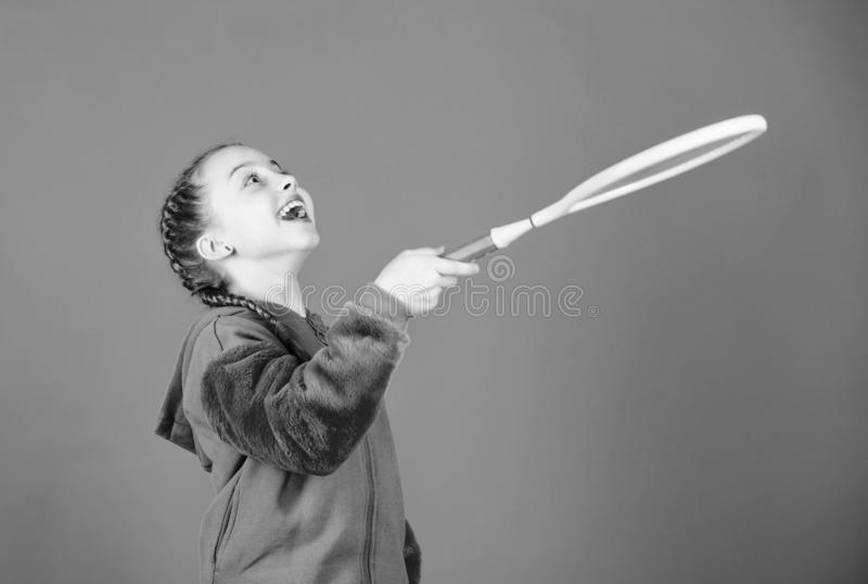 Focused on ball. Tennis sport and entertainment. Girl adorable child play tennis. Practicing tennis skills and having. Fun. Athlete kid tennis racket on blue stock images