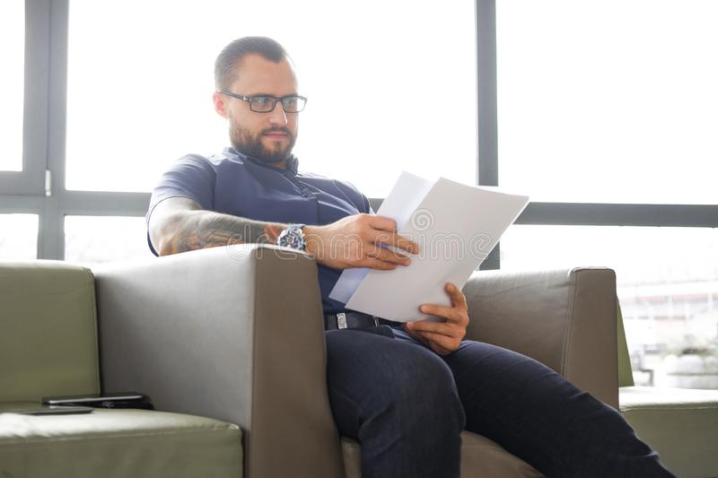 Focused bearded businessman dressed in a blue shirt sitting on the couch and examines important documents in the office royalty free stock photo