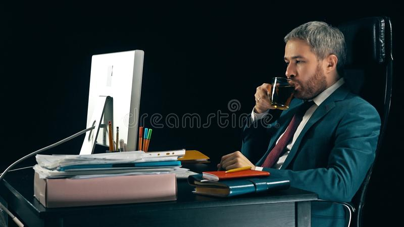 Focused bearded businessman working at his workplace and drinking tea. Black background stock photography