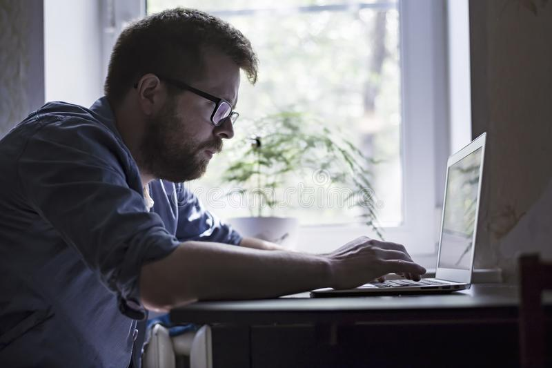 Focused bearded man in glasses works with a laptop at home, against the window background, in the early morning. stock photo