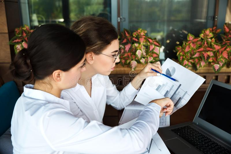 Focused beautiful young businesswomen working on laptop in street cafe outdoor royalty free stock images