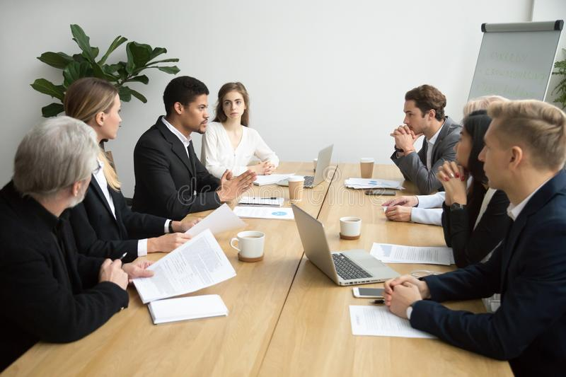 Focused black team leader talking to colleagues at group meeting stock images