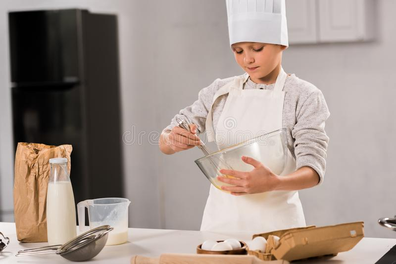 Focused boy in chef hat and apron whisking eggs in bowl at table. In kitchen royalty free stock photos