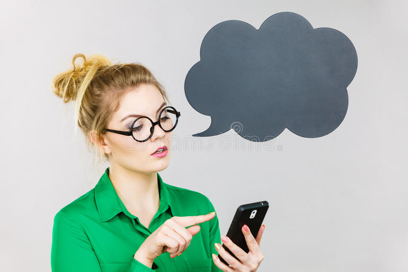 Focused business woman looking at phone, thinking bubble. Focused business woman wearing green shirt and red eyeglasses looking at phone with black thinking or stock photo