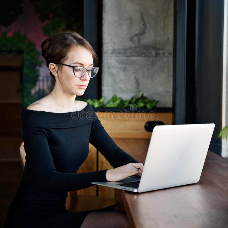Focused business woman sit on cafe working on laptop, concentrated serious female working with computer and notebook in coffee sho royalty free stock photos