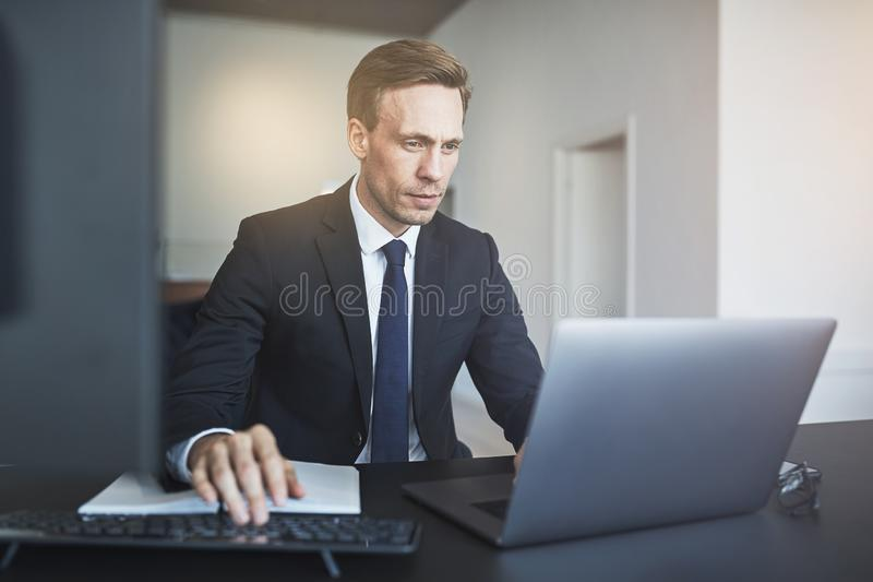 Businessman working online with a laptop at his office desk stock photo