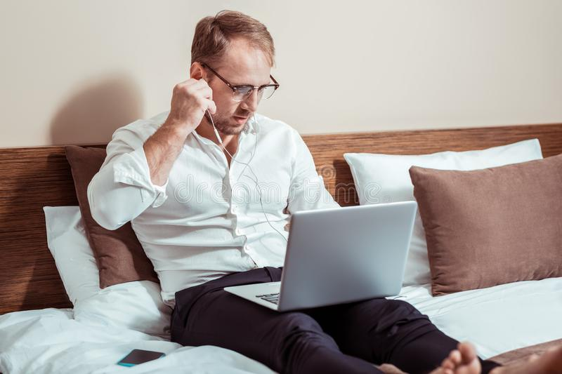 Focused businessmen in white shirt sitting in the bed with laptop royalty free stock images