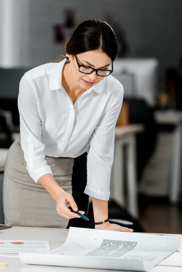 Focused businesswoman in eyeglasses doing paperwork. In office royalty free stock photography