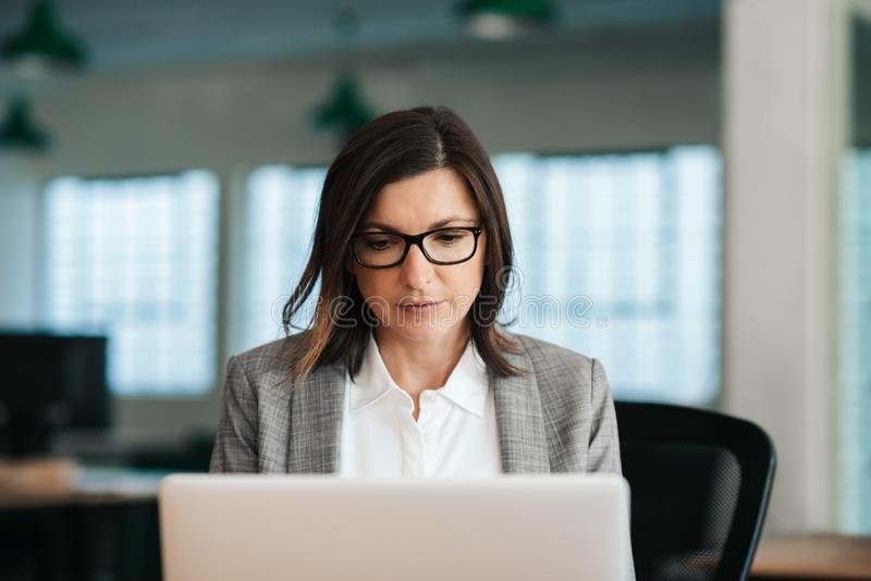 Focused businesswoman sitting at her desk working on a laptop. Focused businesswoman sitting alone at her desk in a large modern office in the late afternoon stock photos