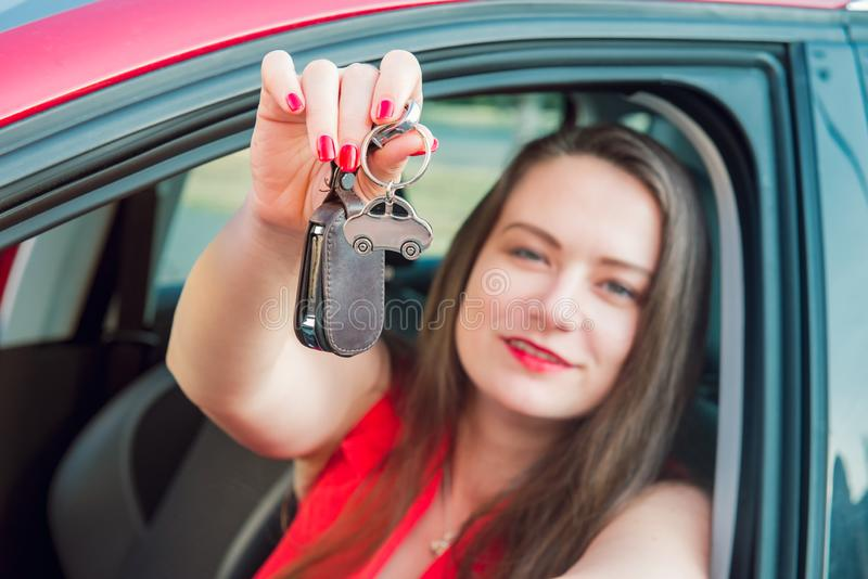 Focused car shaped keychain with keys on the background of happy successful woman sitting in her new car. Outdoors view. Selective stock photo