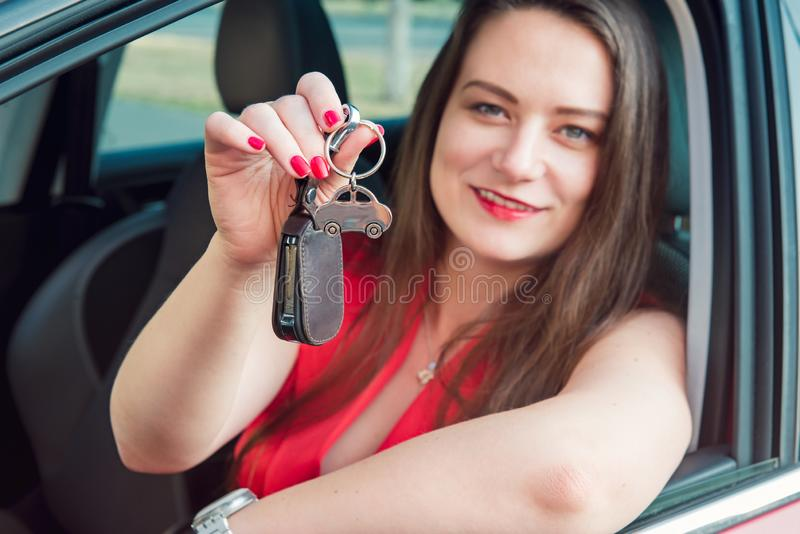 Focused car shaped keychain with keys on the background of happy successful woman sitting in her new car. Outdoors view. Selective. Focus, copy space royalty free stock image