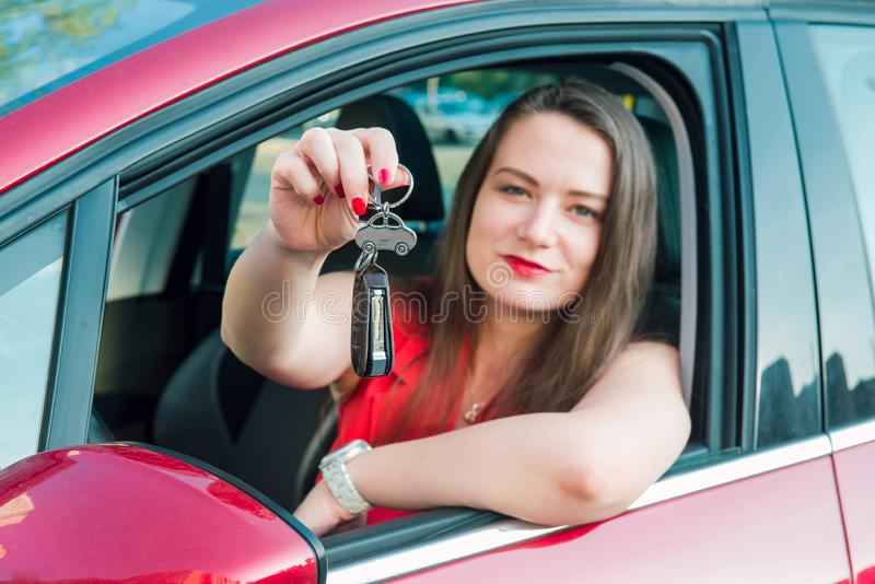 Focused car shaped keychain with keys on the background of happy successful woman sitting in her new car. Outdoors view. Selective. Focus, copy space royalty free stock images