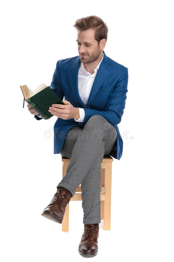 Focused casual guy reading a book while sitting. With his legs crossed and wearing a suit on white studio background royalty free stock images